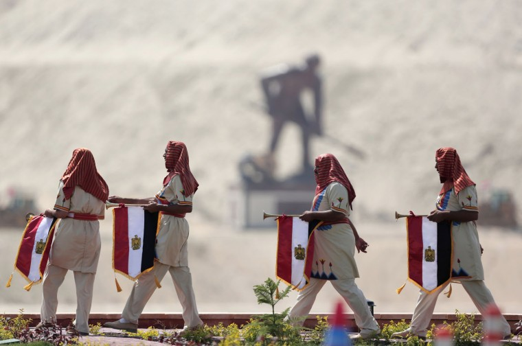 Egyptians wear Pharaonic costumes as they march in front of a statue representing a man digging the new section of the Suez Canal in Ismailia, Egypt, Thursday, Aug. 6, 2015. With much pomp and fanfare, Egypt on Thursday unveiled a major extension of the Suez Canal whose patron, President Abdel-Fattah el-Sissi, has billed as an historic achievement needed to boost the country's ailing economy after years of unrest. (AP Photo/Hassan Ammar)