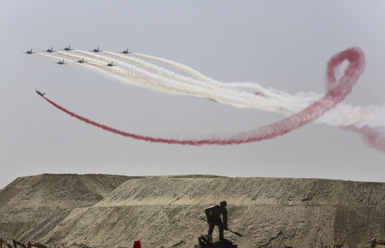 Egyptian air force planes parade in front of a statue representing a man digging during the inauguration ceremony of the new section of the Suez Canal in Ismailia, Egypt, Thursday, Aug. 6, 2015. With much pomp and fanfare, Egypt on Thursday unveiled a major extension of the Suez Canal whose patron, President Abdel-Fattah el-Sissi, has billed as an historic achievement needed to boost the country's ailing economy after years of unrest. (AP Photo/Amr Nabil)