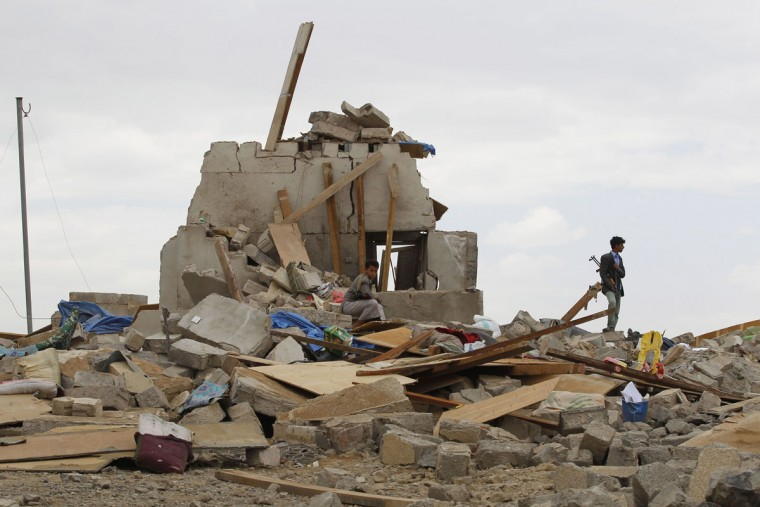 Shiite fighters known as Houthis stand on the rubble of a house destroyed by a Saudi airstrike in Sanaa, Yemen, Wednesday, Aug. 26, 2015. (AP Photo/Hani Mohammed)