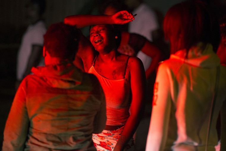 A young woman cries at the scene of a shooting at the Boys and Girls Club on Genesee Street, early Thursday, Aug. 20, 2015, in Rochester, N.Y. The gunman shot into a crowd that gathered outside the club after a basketball game, fatally wounding several people. (Lauren Petracca/Democrat & Chronicle via AP)