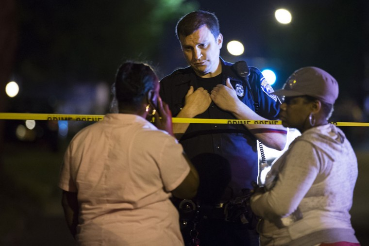 A police officer speaks to bystanders at the scene of a drive-by shooting at the Boys and Girls Club on Genesee Street, early Thursday, Aug. 20, 2015, in Rochester, N.Y. The gunman shot into a crowd that gathered outside the club after a basketball game, fatally wounding several people. (Lauren Petracca/Democrat & Chronicle via AP)