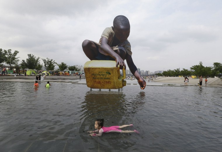 A girl swims to escape a heat in front of a large cutout that raises awareness on water shortage, at the Han River Park in Seoul, South Korea, Tuesday, Aug. 4, 2015. A heat wave warning was issued in Seoul as temperatures soared above 32 degrees Celsius (89.6 Farenheit). (AP Photo/Ahn Young-joon)
