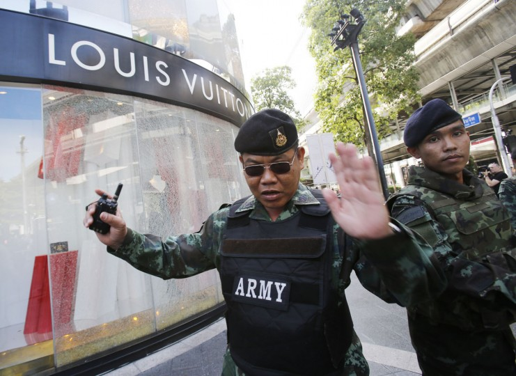 Soldiers move onlookers back from the shattered windows of a Louis Vuitton shop at Gaysorn shopping plaza across from the Erawan Shrine at Rajprasong intersection in Bangkok, Thailand, Tuesday, Aug. 18, 2015, as investigations continue the morning after an explosion. Thailand's prime minister on Tuesday promised that authorities would quickly track down those responsible for the central Bangkok bombing, which he described as the country's worst attack ever. (AP Photo/Sakchai Lalit)