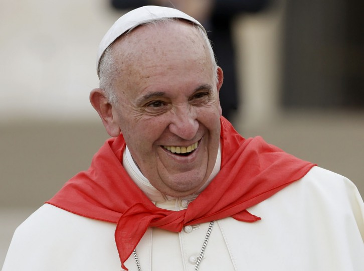 Pope Francis, wearing a red scarf, has a light moment as he leaves St. Peter's Square at the Vatican after an audience with with Altar boys and girls Tuesday, Aug. 4, 2015. (AP Photo/Gregorio Borgia)