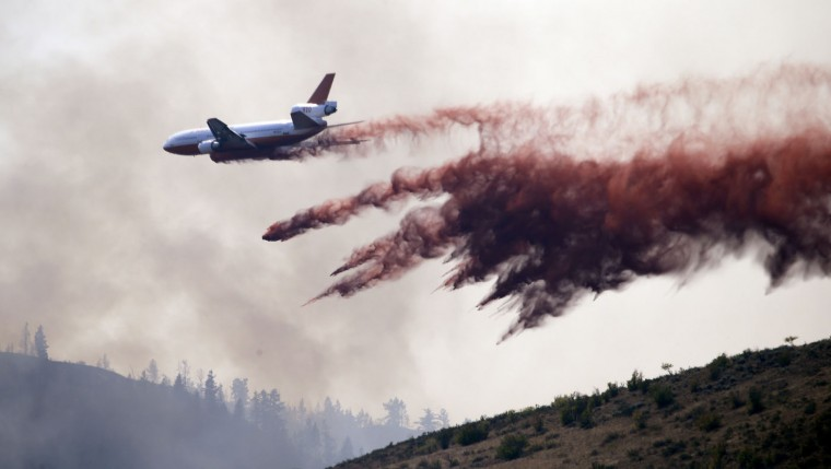 A tanker begins to pull up after dropping a load of fire retardant along a smoldering hillside Thursday, Aug. 20, 2015, in Twisp, Wash.a day after three firefighters were killed fighting a wildfire near the town. Firefighters on several fronts are fighting against raging wildfires advancing on towns in the north-central part of the state. (AP Photo/Elaine Thompson)