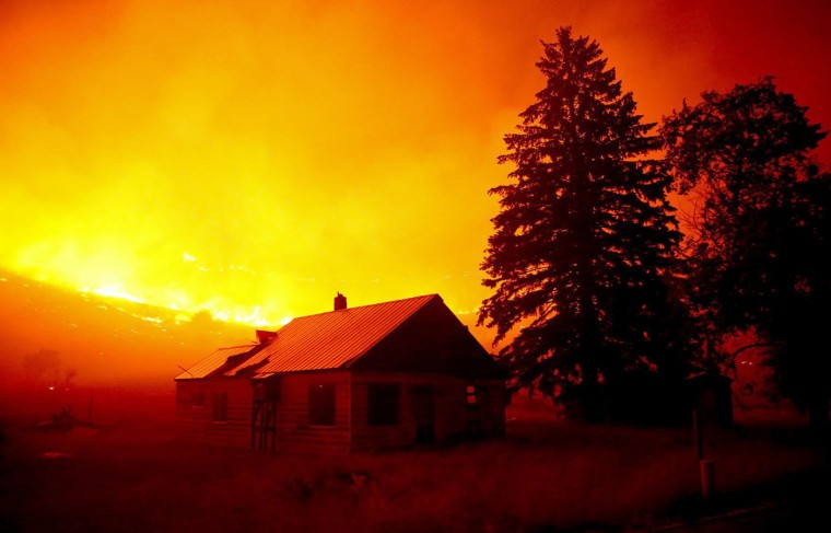 Flames blanket the hillsides on Twisp River Road just outside of the town of Twisp, Wash., early Thursday, Aug. 20, 2015. Firefighters on several fronts are fighting against raging wildfires advancing on towns in the north-central part of the state. (Erika Schultz/The Seattle Times via AP)