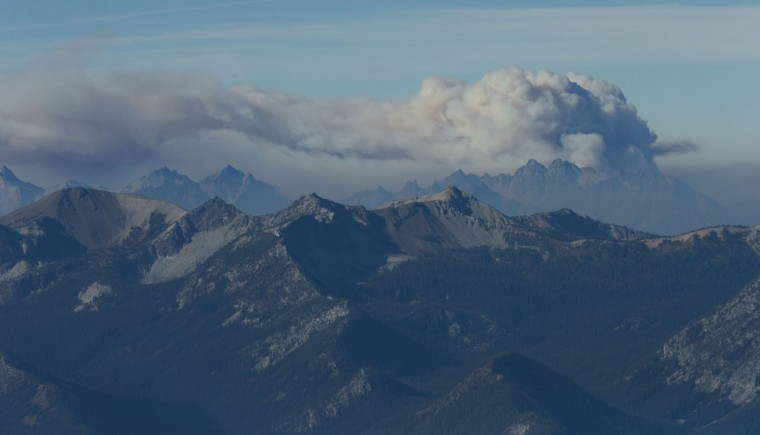 In this aerial photo, smoke from a wildfire rises above the North Cascades in Washington, Thursday, Aug. 20, 2015. Firefighters on several fronts are fighting against raging wildfires advancing on towns in the north-central part of the state. (Bettina Hansen/The Seattle Times via AP)