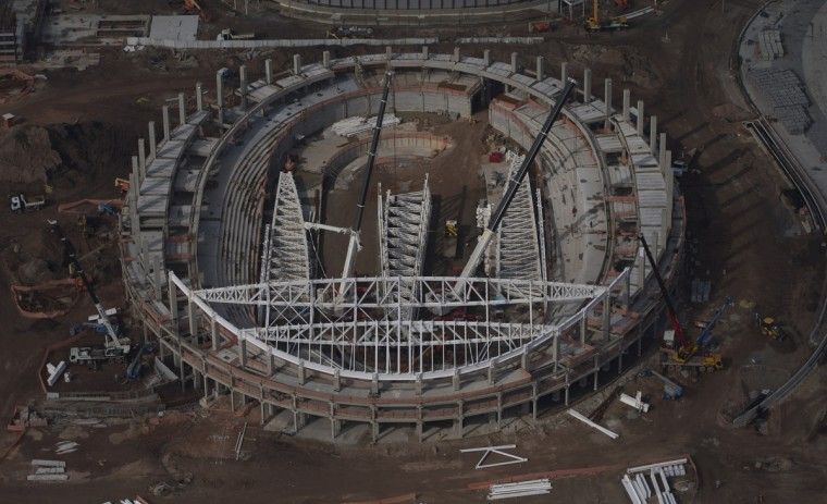 Construction crews work on the velodrome at the Olympic Park for Rio's 2016 Olympics, in Rio de Janeiro, Brazil, Monday, July 27, 2015. A study by Said Business School at Oxford University of Olympic Games since 1960 showed each one had cost overruns. This one is expected to be no different. (AP Photo/Leo Correa)