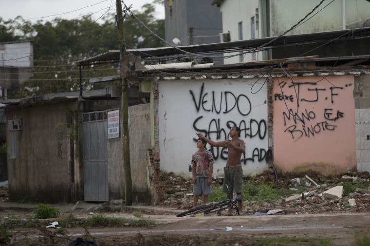 In this July 23, 2015 photo, boys fly kite at the Vila Autodromo slum, in Rio de Janeiro, Brazil. The slum is being demolished to build part of the Olympic Park for the 2016 Rio Olympics, with some residents holding out for better compensation from the city. (AP Photo/Silvia Izquierdo)