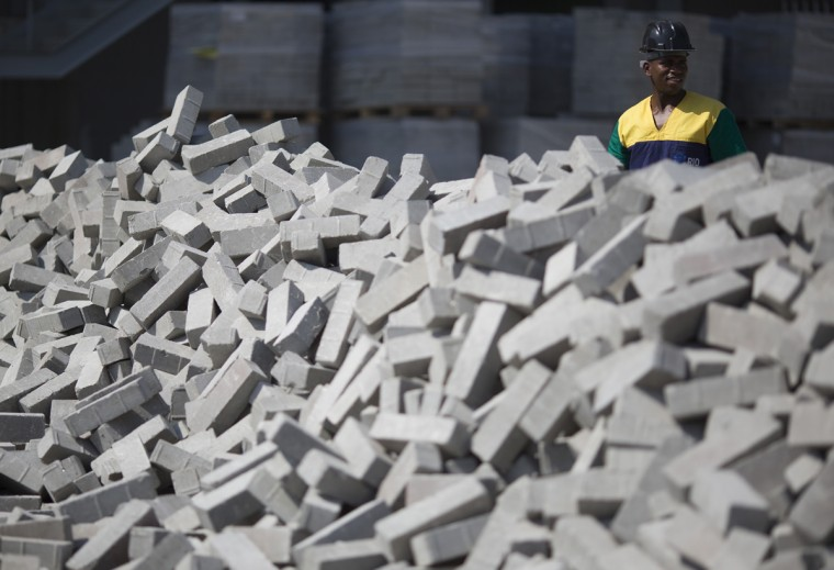 A construction worker stands behind a pile of bricks as he helps build the arena that will host Olympic handball, at Olympic Park in Rio de Janeiro, Brazil, Wednesday, Aug. 5, 2015. Rio de Janeiro Mayor Eduardo Paes said on Wednesday all the venues for South America's first games are on track to be ready when the curtain comes up on Aug. 5 next year. (AP Photo/Leo Correa)