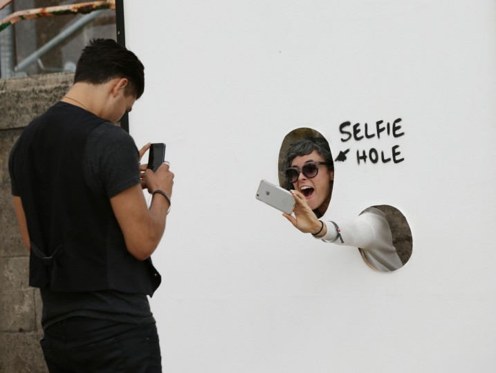 A visitor photographs herself through a 'selfie hole' at Banksy's biggest show to date, entitled 'Dismaland', during a press viewing in Western-super-Mare, Somerset, England, Thursday, Aug. 20, 2015. (Yui Mok/PA Wire via AP)