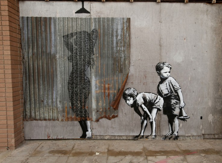 A Banksy piece is displayed at his biggest show to date, entitled 'Dismaland', during a press viewing in Western-super-Mare, Somerset, England, Thursday, Aug. 20, 2015. (Yui Mok/PA Wire via AP)