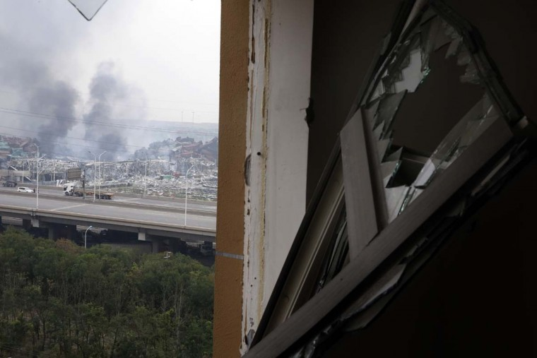 A window shattered by shock waves lies near the site of an explosion at a warehouse in northeastern China's Tianjin municipality, Friday, Aug. 14, 2015. Rescuers pulled out a firefighter trapped for 32 hours after responding to a fire and huge explosions in the Chinese port city as authorities dealt Friday with a fire still smoldering amid potentially dangerous chemicals.  || CREDIT: NG HAN GUAN - AP PHOTO