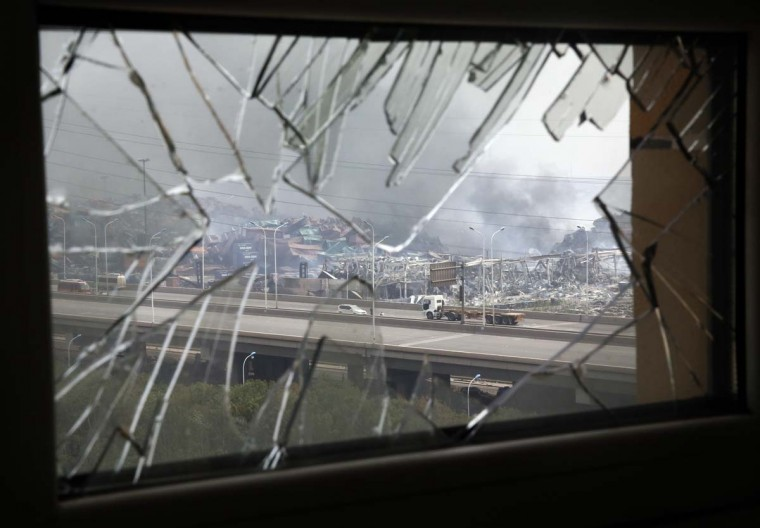 A window shattered by  shock waves frames the site of an explosion at a warehouse in northeastern China's Tianjin municipality, Friday, Aug. 14, 2015. Explosions that sent huge fireballs through China's Tianjin port have disrupted the flow of cars, oil, iron ore and other items through the world's 10th largest port.  || CREDIT: NG HAN GUAN - AP PHOTO