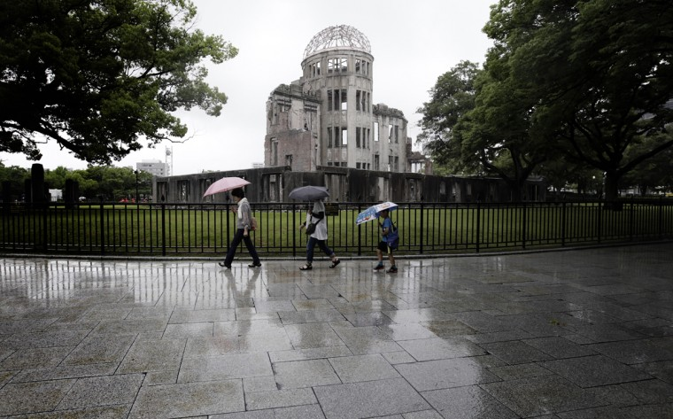 In this July 4, 2015 photo, visitors walk in the rain next to now known as Atomic Bomb Dome in Hiroshima, western Japan. On Aug. 6, 1945, a U.S. plane dropped an atomic bomb on Hiroshima, the first nuclear weapon has been used in war. Japan surrendered on Aug. 15, ending World War II. (AP Photo/Eugene Hoshiko)