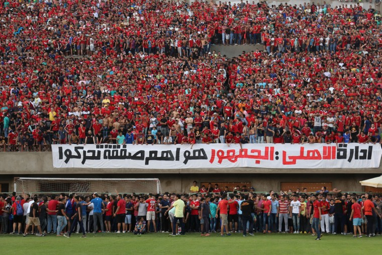 "Ultras Ahlawy, the hardcore fan base of Al-Ahly football club, watch players train at the Al - Ahly club in Cairo, Egypt. Ultras, whose name comes from the Latin word for ìbeyond,î started in Latin America and Europe in the 1950s and eventually made it to Arab countries, with particularly strong followings in North Africa. The first to form in Egypt, Ultras White Knights, emerged in 2007 to support the Zamalek team. Groups backing arch-rival al-Ahly and others soon followed. Arabic on the banner reads, ""the Al-Ahly administration: the fans are the most important group to be moved."" (AP Photo/Mohammed El Raai)"