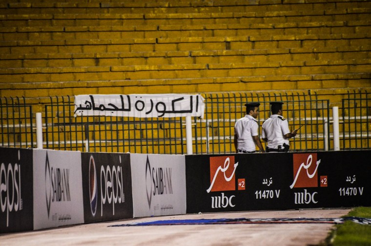 "Security forces walk during a match between Zamalek and ENPPI at the Arab Contractors Stadium, in Cairo. Egyptian authorities have banned fans from attending football games, citing ongoing tension between security forces and Ultras hardcore soccer fan groups since a 2012 stadium disaster in Port Said in which at least 72 football fans were killed. Arabic on the banner reads, ""soccer is for fans."" (AP Photo/Mohammed El Raai)"