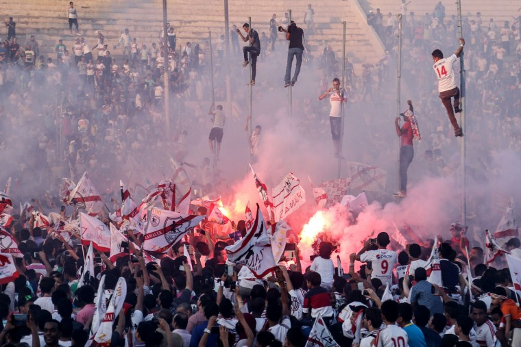 Zamalek soccer fans celebrate after winning the Egyptian League at the Zamalek Sports Club, in the Air Defense Stadium in Cairo, Egypt. The hardcore fan base Ultras White Knights did not celebrate the winning of the team out of respect for more than 20 soccer fans who were crushed to death outside the Air Defense Stadium in Cairo after police fired tear gas to break up the crowd waiting in a fenced, narrow corridor to watch. Police accused the fans of attacking the force, and rioting to enter the stadium on Feb. 8, 2015. (AP Photo/Mohammed El Raai)
