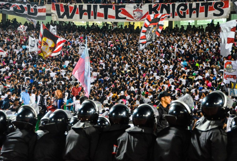 The Zamalek football clubís hardcore fan group Ultras White Knights (UWK) cheer as security forces stand guard during a soccer match between Zamalek and AS Douanes, during the Confederation of African Football (CAF) Champions League at the Cairo Stadium, in Egypt. Zamalek won 2-0. Banners with the face of a boy, depict Amr Hussein, 18, who was killed on Sept. 23, 2013, during clashes between the Ultras members and security forces. (AP Photo/Mohammed El Raai)