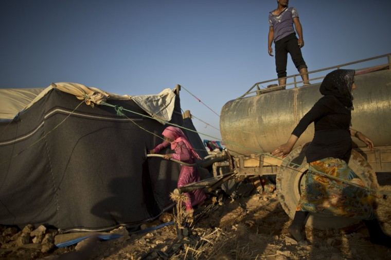 In this Saturday, July 25, 2015 photo, a Syrian refugee girl fills water from a tanker to her tent at an informal tented settlement near the Syrian border on the outskirts of Mafraq, Jordan. Aid agencies asked for $4.5 billion for 2015 to help refugees, but have been forced to slash support programs because of large funding gaps. Thatís had a devastating effect on the amount of food aid coming. (AP Photo/Muhammed Muheisen)