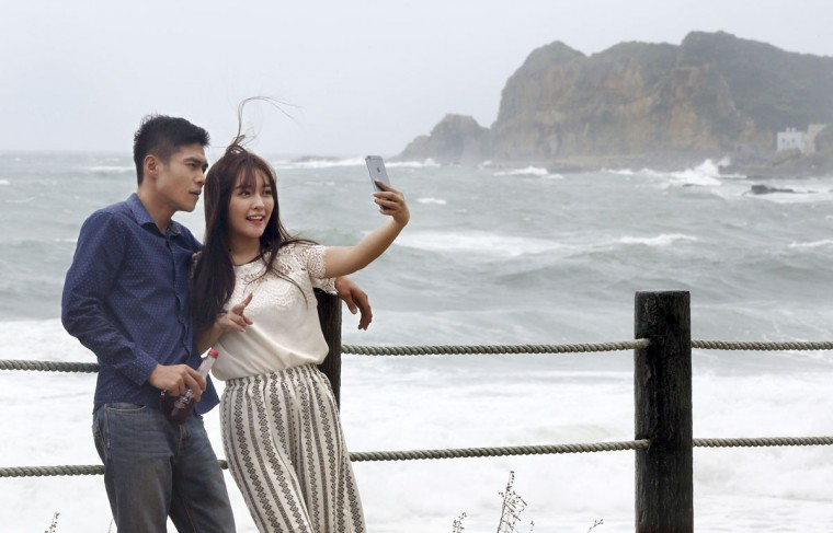 """A couple takes a """"selfie"""" photograph in front of the crashing waves from Typhoon Soudelor off the coast of Keelung, northeastern Taiwan, Friday, Aug. 7, 2015. Soudelor is expected to bring heavy rains and strong winds to the island late Friday with winds speeds over 170 km per hour (100 mph) and gusts over 200 km per hour (120 mph) according to Taiwan's Central Weather Bureau. (AP Photo/Wally Santana)"""