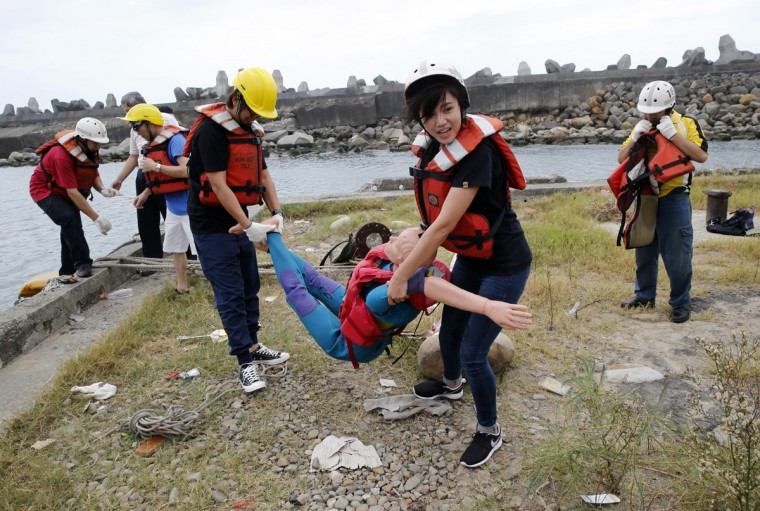"""Employees of commercial ships and fishing vessels """"rescue"""" a dummy during an emergency rescue drill as Typhoon Soudelor approaches in Keelung, northeastern Taiwan, Friday, Aug. 7, 2015. Soudelor is expected to bring heavy rains and strong winds to the island late Friday with winds speeds over 170 km per hour (100 mph) and gusts over 200 km per hour (120 mph) according to Taiwan's Central Weather Bureau. (AP Photo/Wally Santana)"""