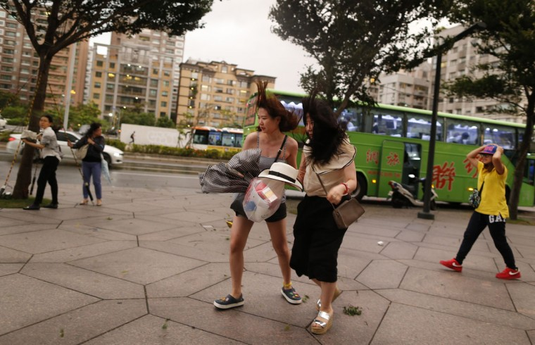 Two women brave the winds from Typhoon Soudelor in Taipei, Taiwan, Friday, Aug. 7, 2015. Soudelor is expected to bring heavy rains and strong winds to the island late Friday with winds speeds over 170 km per hour (100 mph) and gusts over 200 km per hour (120 mph) according to Taiwan's Central Weather Bureau. (AP Photo/Wally Santana)