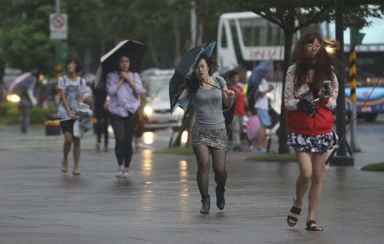 Office workers brave the strong winds from Typhoon Soudelor in Taipei, Taiwan, Friday, Aug. 7, 2015. Soudelor is expected to bring heavy rains and strong winds to the island late Friday with winds speeds over 170 km per hour (100 mph) and gusts over 200 km per hour (120 mph) according to Taiwan's Central Weather Bureau. (AP Photo/Wally Santana)