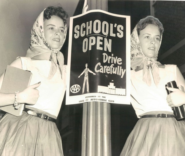 September 5, 1956 - Melba O'Brien and Shelba O'Brien of 4206 Thayer Court standing beside poster in front of Southern High School. They are entering 11th grade. (Clarence B. Garrett/Baltimore Sun)