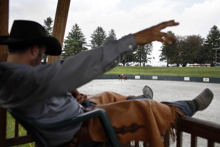A cowboy signals rider Kevin Hittinger before the start of a competition round. (Tom Brenner, Baltimore Sun)