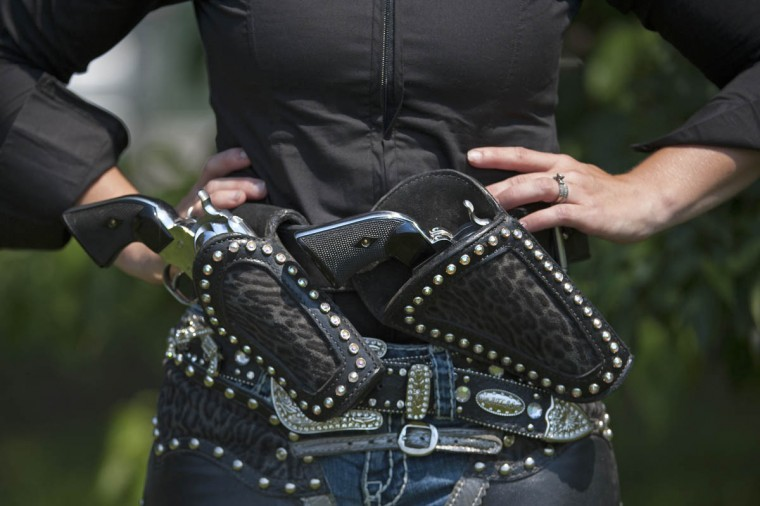 A cowgirl shows off her .38 caliber pistols between competition stages. Authentic single action pistols can cost up to $1000 per pistol. (Tom Brenner, Baltimore Sun)