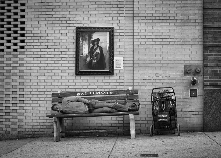 Man laying on bench beneath painting