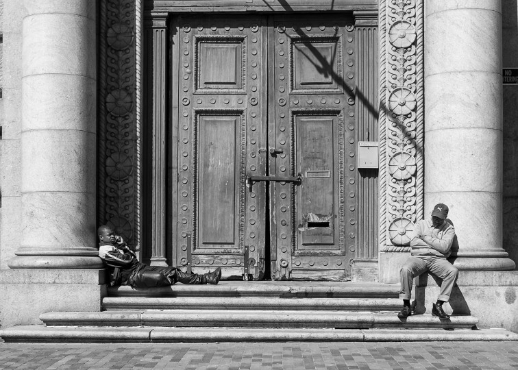 Two men resting by big door