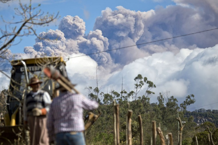 Peasants work with ashes spewed by the Cotopaxi volcano in the background in Sangolqui, Ecuador on August 23, 2015. A dozen towns of central Ecuador, including Quito sector, suffered Saturday the ashes of the Cotopaxi volcano, which started erupting a week ago after 138 years, as crops and cattle were affected. (MARTIN BERNETTI/AFP/Getty Images)
