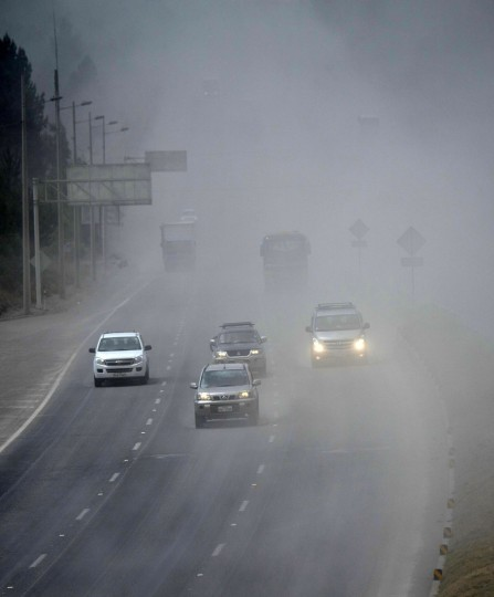 Vehicles drive along a road covered by ashes of the Cotopaxi volcano in Lasso, Ecuador on August 23, 2015. A dozen towns of central Ecuador, including Quito sector, suffered Saturday the ashes of the Cotopaxi volcano, which started erupting a week ago after 138 years, as crops and cattle were affected. (MARTIN BERNETTI/AFP/Getty Images)