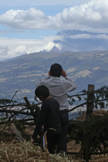 People look at the Cotopaxi volcano as it spews ashes in Quito, Ecuador on August 22, 2015. Ash from Ecuador's Cotopaxi volcano rained down on a dozen villages in the country's central Andean region Saturday, where agricultural output has been marred by a blanket of soot from explosions that began a week ago. (JUAN CEVALLOS/AFP/Getty Images)