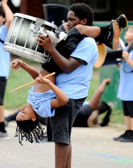 Monyeah Denton is held upside down by Katrell Norman as he plays a snare drum solo during the Boom Squad's performance at Habitat for Humanity's Rock the Block housing celebration event, Saturday, Aug. 29, 2015, in Evansville, Ind. (Darrin Phegley/Evansville Courier & Press via AP)