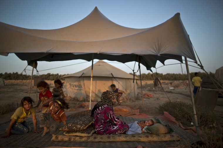 A Syrian refugee sits on the ground next to her child to escape the heat trapped inside their tent, at an informal tented settlement near the Syrian border on the outskirts of Mafraq, Jordan, Saturday, Aug. 22, 2015. (Muhammed Muheisen/Associated Press)