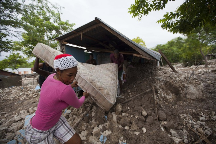 Residents salvage a mattress from a home partially submerged in mud from a mudslide triggered by Tropical Storm Erika, in Montrouis, Haiti, Saturday, Aug. 29, 2015. Erika dissipated early Saturday, but it left devastation in its path on the small eastern Caribbean island of Dominica, and parts of Haiti authorities said. (Dieu Nalio Chery/Associated Press)