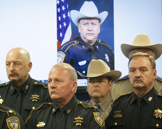 Law enforcement officers attend a news conference regarding the shooting death of Harris County Sheriff's Deputy Darren Goforth, Saturday, Aug. 29, 2015, in Houston. Prosecutors on Saturday charged Shannon J. Miles with capital murder in the Friday killing of Goforth at a suburban Houston gas station. (Marie D. De Jesus/Houston Chronicle via AP)