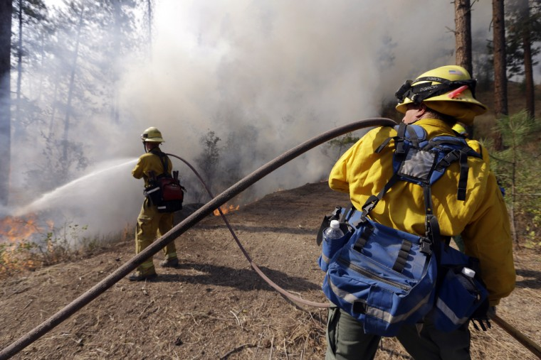 """Firefighters hose the edge of a controlled fire along a driveway being used as a fire break between houses and the main fire Saturday, Aug. 22, 2015, in Okanogan, Wash. Out-of-control blazes in north-central Washington have destroyed buildings, but the situation is so chaotic that authorities have """"no idea"""" how many homes may have been lost. (Elaine Thompson/Associated Press)"""