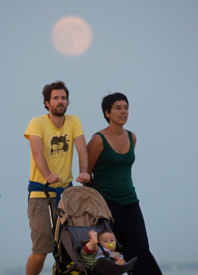 """A young couple strolls along the Tagus river bank in Lisbon as a so-called """"supermoon"""" full moon rises Saturday, Sat. 29 2015. Supermoon, or perigee moon, is the name given when the full or new moon comes closest to the Earth making it appear bigger. Saturday's full moon supermoon is the first of the three that will occur in 2015.(Armando Franca/Associated Press)"""