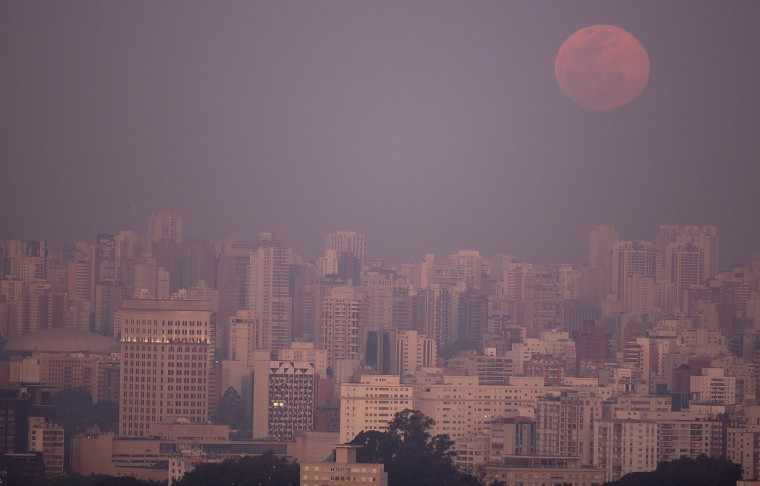 A supermoon rises over the skyline in Sao Paulo, Brazil, Saturday, Aug. 29, 2015. The phenomenon, which scientists call a perigee moon, occurs when the moon is near the horizon and appears larger and brighter than other full moons. (Andre Penner/Associated Press)