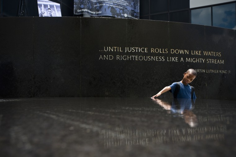 Benjamin Levett, 6, runs his hands through the Civil Rights Memorial fountain during a memorial to honor civil rights leader Julian Bond held by the Southern Poverty Law Center on Saturday, Aug. 22, 2015, in Montgomery, Ala. Bond died on Aug. 15, 2015, in Fort Walton Beach, Florida, at 75. (Albert Cesare /The Montgomery Advertiser via AP)
