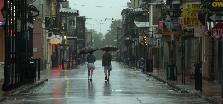 August 28, 2005 -  As the rain begins to fall in the French Quarter, two men walk through the mostly empty streets of New Orleans enjoying the moment as Hurricane Katrina approached the city. (John Makely/Baltimore Sun)