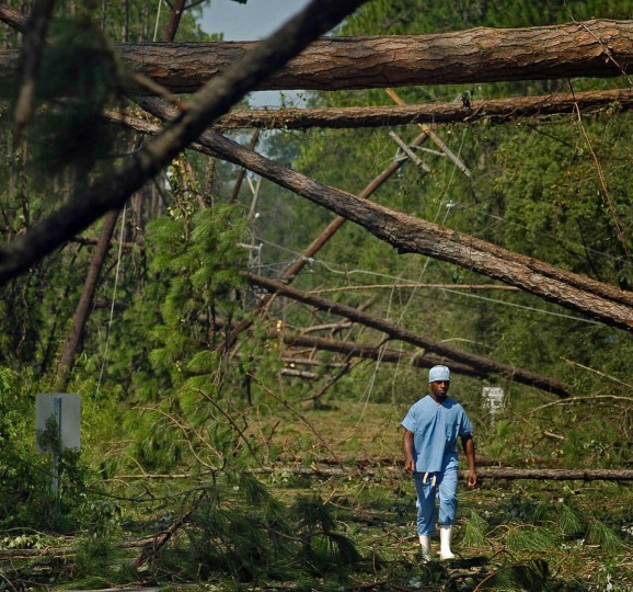 August 30, 2005 - On break from his job, clinical technician Brian Johnson walks up Three Rivers Rd, below downed trees and power lines to check the damage to the area in Covington one day after residents try to move on in the aftermath of Hurricane Katrina. (Karl Merton Ferron/Baltimore Sun)