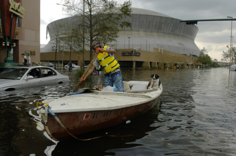 August 31, 2005  - After Hurricane Katrina made it's way through New Orleans, a boater with his dog floats past the Superdome. (John Makely/Baltimore Sun)