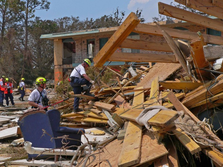 """August 31, 2005 - The aftermath of Hurricane Katrina in Ocean Springs, Mississippi.  Search Specialists Mike King (left) and Tom Feehan hold """"SearchCams,"""" apparatus that can extend to look for victims as they climb the rubble of a two- story collapsed apartment complex which had been destroyed by a massive surge. The search team was sent by FEMA. (Karl Merton Ferron/Baltimore Sun)"""