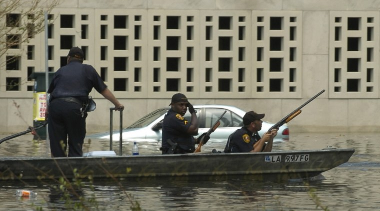 August 31, 2005  - Police in a small boat patrol the flooded streets of New Orleans looking for people needing rescue and looters. (John Makely/Baltimore Sun)
