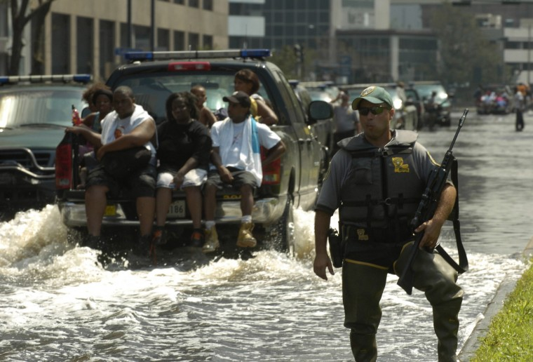 August 31, 2005 - A Natuaral Resources officer guards police boats and equipment from looters downtown as a group of refugees gets a ride to a shelter in a police pickup truck. (John Makely/Baltimore Sun)